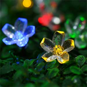 Multi Colored Solar Flower String Lights Hanging On A Bush In Landscaping
