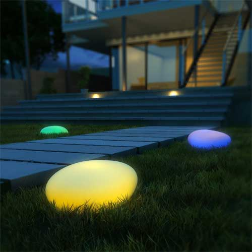 Multi-Colored Large Stone-Shaped Solar Globe Lights at Night in Backyard